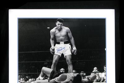 Huge black and white photo of Muhammed Ali, shown glowering over Sonny Liston, signed by Ali using a blue Sharpie and double matted in a 35 inch by 29 ½ inch frame (est.  $800-$1,000).