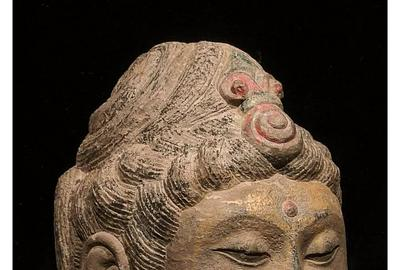 China, Tang Dynasty gilded stone head of Buddha with two-tiered 'snail-shell' hair curls ornamented by red spiraling 'jewel,' circa 618-907 A.D., 530mm tall on custom stand.  Provenance: Old Somerset (England) collection of Asian art formed in 1980s/1990s.  Estimate £20,000-£40,000