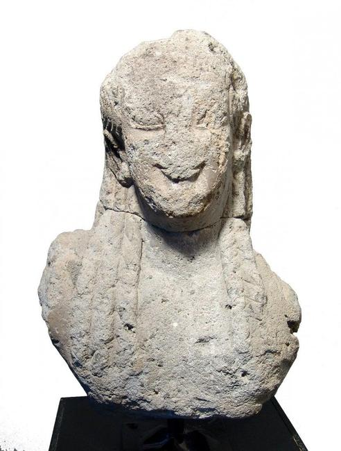 Large Archaic Greek stone head of a Kouros from the 6th century BC, with large, almond shaped eyes and hair in long curled locks, 19 inches tall by 14 inches wide (est. $18,000-$25,000). Ancient Resource Auctions