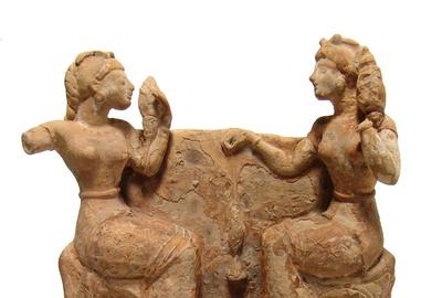 Greek terracotta relief scene from the 5th century BC, depicting two women seated on ornate chairs and facing each other, in conversation as they spin a fiber into yarn (est.  $8,000-$12,000).