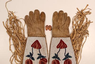 "Pair of Native American ""Gauntlet Gloves"" made from elk skin with elaborate beadwork, circa 1900-1920, by one of the Northern Plains Tribes, plus a pair of tiny fantasy moccasins ($500)."