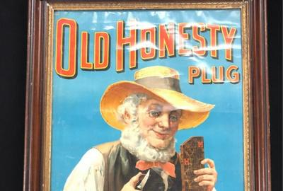 "Framed advertising poster for Old Honesty plug tobacco (""Never Varies, Always the Best""), depicting a bearded man cutting off a piece of plug, plus a plug tobacco bag (est.  $100-$200)."