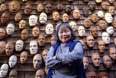 Ruth Asawa with life masks on the exterior wall of her house.  (Image credit: Photography by Terry Schmitt.  ARTWORK: Untitled (Wall of Masks), c.  1966–2000.  Ceramic, bisque-fired clay.  © 2020 Estate of Ruth Asawa/ Artists Rights Society (ARS), New York.  Courtesy The Estate of Ruth Asawa and David Zwirner)