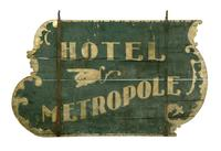 "Lot 468 to sell at Garth's March 15 auction.  HOTEL SIGN.  Massachusetts, mid-19th century, wood.  Double-sided sign with ""Hotel Metropole"" and a pointing hand.  Wear.  36""h.  55.5""w., not including hanging brackets.  This sign originally hung near the Hotel Metropole in Brookfield, Massachusetts.  Included with the lot art two copies of photographs: one of the Metropole, and the other a town view with a horse-drawn pumper and this sign hanging on the lightpost pointing toward the Metropole.  Es"