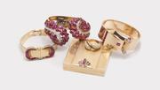 A selection of jewelry from The October Auction including a Van Cleef & Arpels covered wristwatch, a Boucheron carved ruby cuff bracelet, and a Raymond Yard compact.