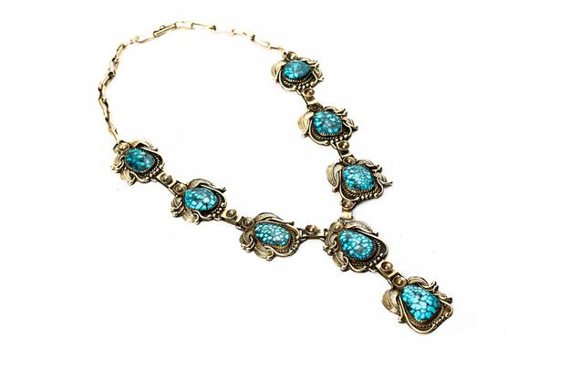 "Lot 32: Andy Lee Kirk, Squash blossom necklace with eight pendants of Battle Mountain turquoise set in 14k gold handtooled leaves and floral stations.  Two of the pendants form a center drop.  16"" l.  3""l.  pendant drop.  76.1g.  Estimate $4000-6000"