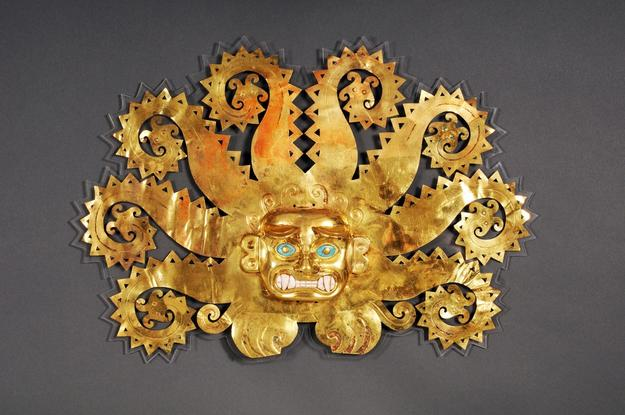 Mochica, north coast, possibly La Mina Forehead Ornament with Feline Head and Octopus Tentacles Ending in Catfish Heads 100–800 A.D.  Gold, chrysocolla, shells, 28.5 x 41.4 x 4.5 cm Lima, Museo de la Nación.  Photo: Daniel Giannoni