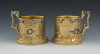 A Pair of Russian Silver and Gold Wash Trompe L'Oeil Tea Glass Holders, Marks of Ivan Khlebnikov with Imperial Warrant, Moscow, ca.  1900