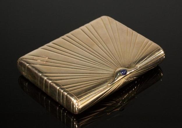 Lot 374: FABERGE 14K YELLOW GOLD AND SAPPHIRE CIGARETTE CASE.  With Russian gold mark for 14k, designed as a rectangular fluted case with cabochon sapphire push-piece, with a signed wooden fitted case.  3 1/2 by 2 3/4 by 1/2 inches, 187 gms.