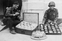 First Lieutenant James J.  Rorimer, at left, and Sergeant Antonio T.  Valin examine recovered objects.  Neuschwanstein, Germany, May 1945.  Photograph by U.S.  Signal Corps