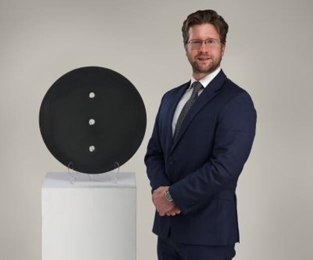 "Malyk pictured with Lucio Fontana's ""Concetto Spaziale,"" which will be offered in the May 1 Modern & Contemporary Art auction"
