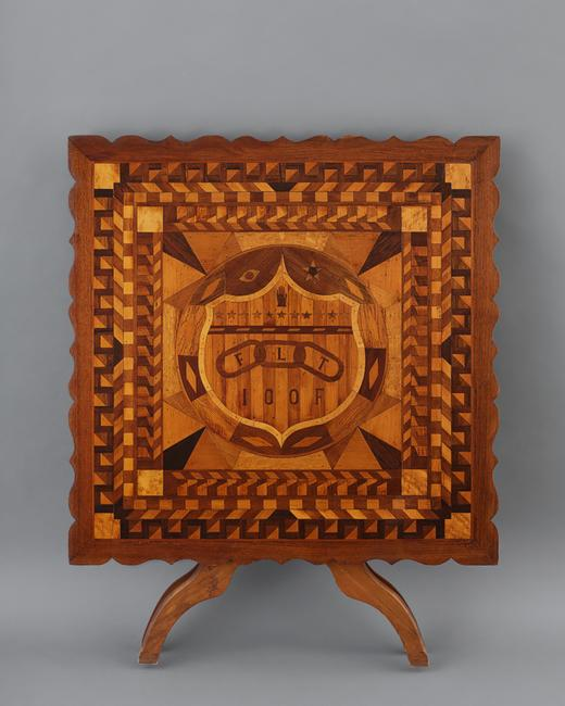 "Independent Order of Odd Fellows Marquetry Table.  James J.  Crozier (1867–1950) Probably Islip, New York, 1933.  Wood, 33 3/4 x 33 3/4 x 27 1/4."" Collection American Folk Art Museum, New York Gift of Kendra and Allan Daniel, 2015.1.160"