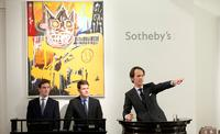 Former auctioneer Tobias Meyer, conducting the auction with Basquiat's Orange Sports Figure behind him, which went on to sell for £4,073,250.