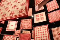 "Installation view of the American Folk Art Museum's ""Infinite Variety: Three Centuries of Red and White Quilts,"" a special exhibition at the Park Avenue Armory in Spring 2011."