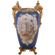 Unmarked, 17.5-inch-tall Wave Crest vase (10 inches across handles), with a hand-painted scenic decor on front and back and gilt metal feet.