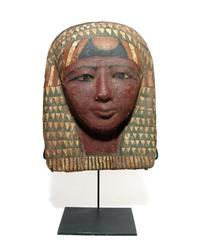 Egyptian painted cartonnage funerary mask (Late Period, circa 664-332 BC), face having a deep red skin tone and with black detailing to the eyes and brow (est.  6,000-$9,000).