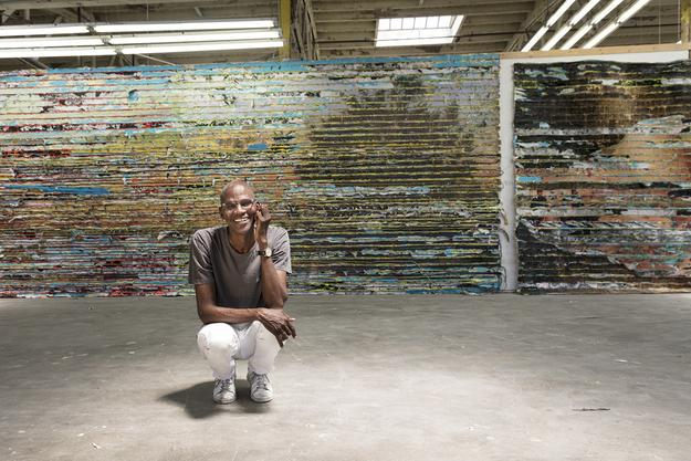 Mark Bradford, seen in his Los Angeles studio with a detail of Pickett's Charge, 2017.  Mixed media.  Courtesy of the artist and Hauser & Wirth.