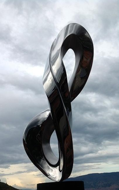 "Santiago Medina's ""Infinity"" is made with highly polished Italian stainless steel and displays in its organic sculptoric form, the infinite symbol.  The sculpture measures 24 inches in height by 12 x 10 inches.  Infinity is pictured in front of the Colombian landscape where it was cast in stainless steel at Medina's studio in Medellin, Colombia and will be shipped to its permanent home at the Tisch Library, Tufts University, Boston, MA."