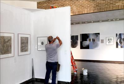 "Carl installing the exhibit ""Colorless & Odorless"" by Edward A.  Burke"