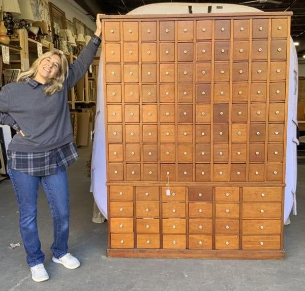 Pam Stone stands next to this rare and massive 104-drawer apothecary library card filing cabinet ($400-800) with hand dovetailing and porcelain knobs, which stands over 72 inches tall.