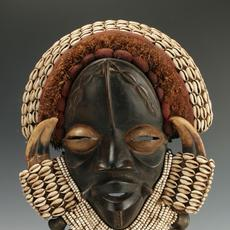 African Dan Guere mask, 23 inches by 10 inches, made from wood, wild boar horn, cowrie shells, beads, textiles, raffia and bronze bells, on a custom stand (est.  $300-$500).