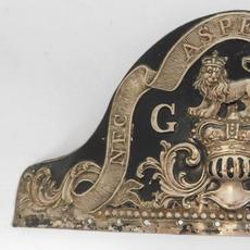 British Royal Warrant of 1768 grenadier cap plate, made sometime between 1768 and 1802 from repousse silver-plated sheet copper over a die-struck tinned-iron plate (est.  $3,000-$5,000).