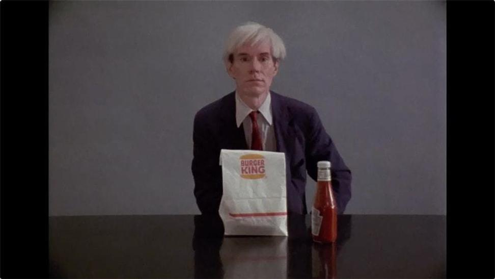 Screenshot of documentary footage showing Andy Warhol having a Whopper, used in a Burger King commercial during the Super Bowl.