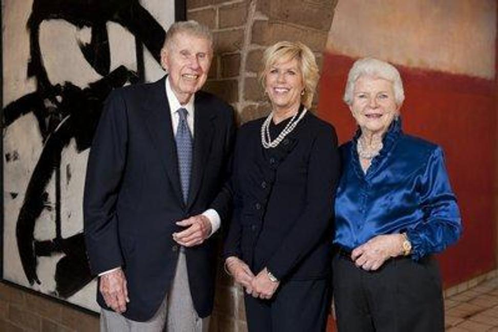 Harry W.  and Mary Margaret Anderson, and their daughter Mary Patricia Anderson Pence, standing in front of Franz Kline, Figure 8, 1952 and Mark Rothko, Pink and White over Red, 1957.  Both are works being donated to Stanford University.
