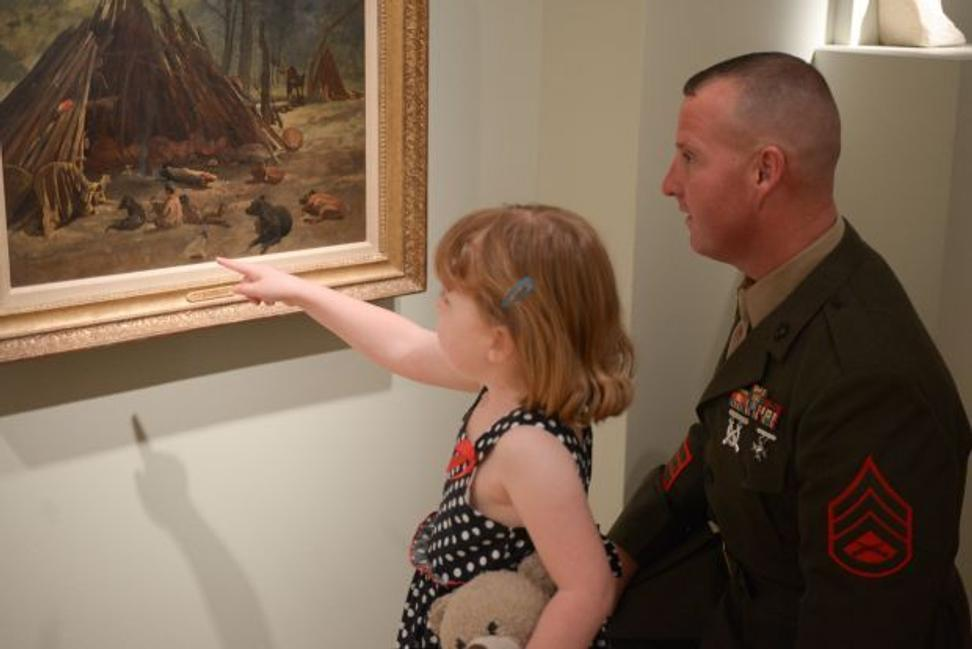 Military man and his daughter looking at art at San Antonio Museum of Art, in the program Blue Star Museums, a collaboration among the National Endowment for the Arts, Blue Star Families, the Department of Defense, and more than 2,000 museums across America to offer free admission to the nation's service members.