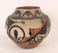 Polychrome Acoma olla, circa 1904, with bands of checkerboard decoration in black enclosing red abstract design.