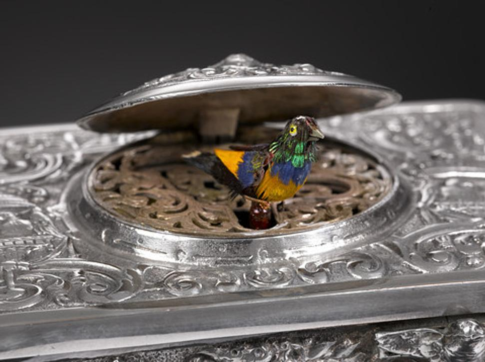 The Rococo design of the sterling silver musical bird box shown here typifies the elaborate mechanism and design work prevalent in that era.  The filigree design and scroll work hides a brightly feathered bird which pops out and chirps a song and flutters its wings before disappearing back into the box.