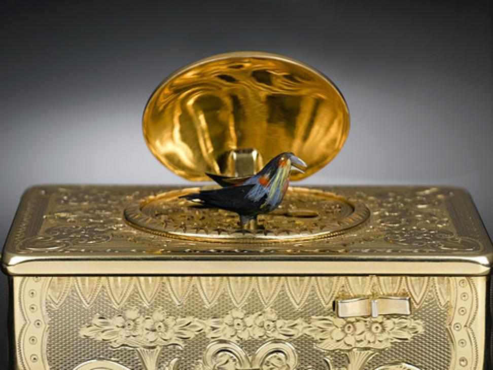 This remarkable gold engraved singing bird music box executed in the Rococo design features not only a delicate feathered creature, but a magnificent painted medallion depicting a pastoral scene of a couple courting.  Made by the house of E.  Ruhl (ca.  1900), this example of an automated bird is beyond compare.