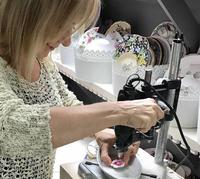 Mary-Ann Wood painstakingly hand-makes each DinnerWear Jewelry piece herself, using tools like the drilling machine she's seated at here.