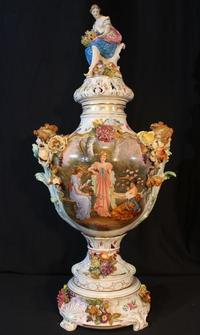 Large, hand-painted Dresden capped urn with applied flowers and a scene with Greek girls, 29 inches tall.