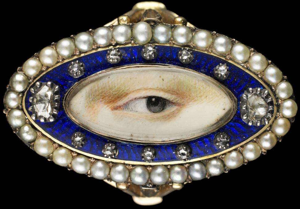 Rose gold oval ring surrounded by a blue enamel border containing ten small and two large diamonds enclosed in a border of natural split pearls, ca.  1790.  Brown left eye.  Purchased from Edith Weber, New York.  Dimensions: 3⁄4 × 1 1⁄4 × 7⁄8 in.