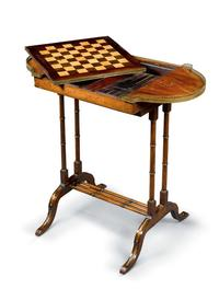 After a Design by John Maclean, BACKGAMMON AND CHESS TABLE, the pull-out top with inlaid chess board to one side over a tooled leather interior playing surface brass, parcel-gilt, boxwood stringing, rosewood, satinwood, leath er, 76.5 by 82 by 43cm., 30 by 32¼ by 17in.  19th century.  Made circa 1810.