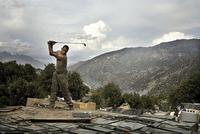 Tim Hetherington, Afghanistan, Korengal Valley, Kunar Province, Sterling Jones practices his golf swing while at the main KOP [Korengal Outpost] firebase in the valley.  Soldiers spend about two weeks at the Restrepo outpost before coming back to the main KOP base, where they can get a hot shower and call their family., April 2008.  Chromogenic (Lightjet) digital print.  Courtesy Estate of Tim Hetherington.  © Tim Hetherington, Magnum Photos