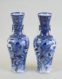 A pair of Japanese blue and white baluster vases with applied cicada decoration.