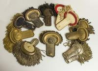 A lot of 17 sets of various epaulets includes a single child or young cadet's uniform epaulet of gold embroidered brush with a brass button, a number of pre-Civil War epaulets and more.