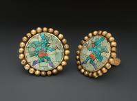 In Golden Kingdoms: Luxury and Legacy in the Ancient Americas: Pair of Earflares, Winged Messengers, 200s–600s CE, made in Peru (Moche culture).  Gold, turquoise, sodalite, and shell, 3 3/16 in.  diam.  The Metropolitan Museum of Art, New York, Gift and Bequest of Alice K.  Bache, 1966.  66.196.40-.41