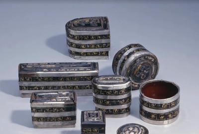 A Set of Seven Black-lacquer Boxes with Silver and Gold Appliqué   China, Western Han dynasty (2nd-1st c.  BCE) Lengths range from 4.0 to 15.0 cm.  (1 1/2 to 5 7/8 in.)