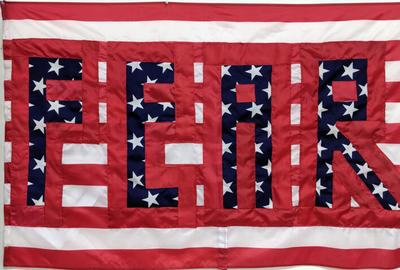 "Sara Peak Convery ""Divided States of America (The FEAR Flag)"", (2019) Printed U S Flags, thread, 34 x 53 inches.  Courtesy the artist."