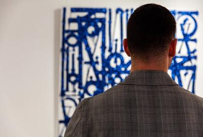 Art investor views RETNA's  Los Ne El Barrio, the abstract lettered painting is finished with a rare blue diamond dust