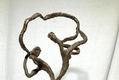 This abstract figural bronze sculpture ($400-600), signed Estelle Goodman, of a man and a woman, with their backs to one another yet connected by a figurative representation of communication in the form of a flowing ribbon between their mouths.  It stands 18¼ inches tall.