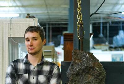 Gallery 63 owner Elijah Brown stands alongside the massive, museum-quality meteorite that will be sold online Tuesday, April 6th, at 11 am Eastern time.  The stand measures 74 inches tall.