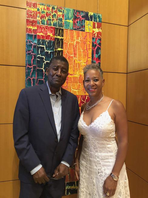 William T.  Williams and Katrina Adams in the United States Tennis Association (USTA) President's Suite on the opening day of the tournament, Arthur Ashe Stadium, Flushing Meadows, NY.  On view: William T.  Williams (b.1942), Taking It Home (111 1/2 Series), 1999, acrylic on canvas, 74 1/4 x 30 1/4 inches / 188.6 x 76.8 cm, signed