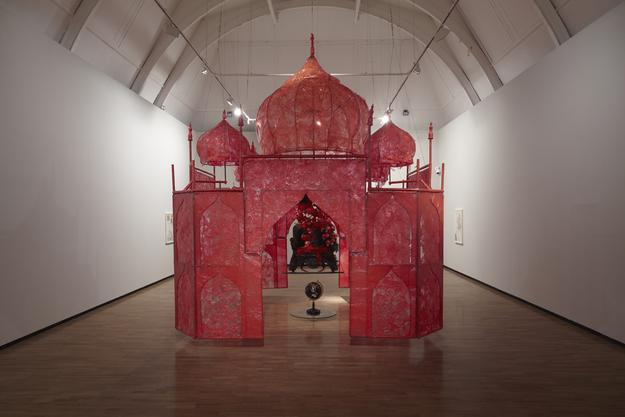 "Rina Banerjee, ""Take me, take me, take me…to the Palace of love,"" 2003.  Plastic, antique Anglo-Indian Bombay dark wood chair, steel and copper framework, floral picks, foam balls, cowry shells, quilting pins, red colored moss, antique stone globe, glass, synthetic fabric, shells, fake birds.  13 x 13 x 18 ft.  Courtesy of artist, RB Storage, NYC."