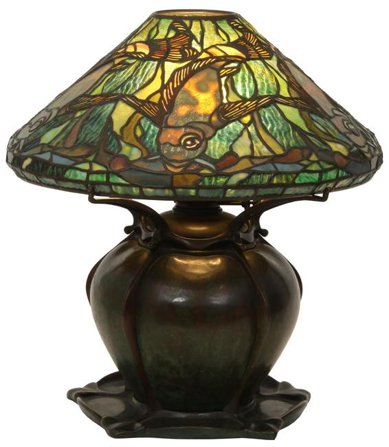 A rare Tiffany Studios leaded glass aquatic fish lamp ($80/100,000) on a bronze pumpkin base has a shade surrounded by five swimming fish in gold mottled glass, 17½ inches tall with a 16- inch diameter shade.