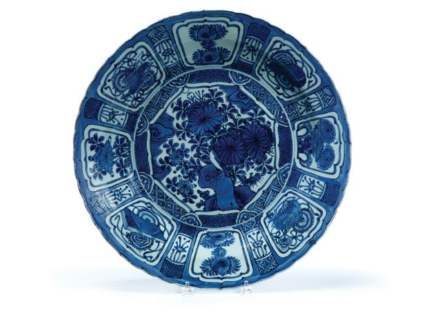 "KRAAKWARE CHARGER OR BASIN.  China, ca.1610-1630.  Blue and white decoration featuring a central medallion of a bird in a garden setting, surrounded by a border of reserves filled with flowers and auspicious symbols.  Scalloped edge.  Two small hairlines.  3.75""h.  19.75""d.  Estimate $ 8,000-10,000"