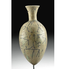 Ancient Egyptian late-18th-Dynasty Amarna faience lotus bottle with glyphs, circa 1353-1336 BCE, 5.626 inches high (7.6 inches with included stand).  Estimate: $15,000-$20,000.